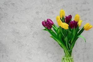 bouquet di fiori di tulipano primaverile viola e giallo in un vaso di vetro su uno sfondo chiaro. copia spazio. festa della mamma. giornata internazionale della donna. foto