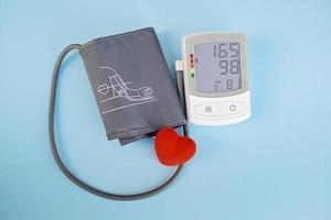 cuore giocattolo rosso e tonometro su sfondo blu. concetto di assistenza sanitaria. cardiologia - prendersi cura del cuore.. foto