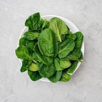 concetto di cibo pulito. foglie di spinaci organici freschi in un piatto su uno sfondo chiaro. sana dieta detox primavera-estate. cibo crudo vegano. foto