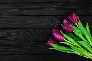 bouquet di fiori di tulipano primavera viola su uno sfondo di legno nero. posa piatta. copia spazio. festa della mamma. giornata internazionale della donna. foto