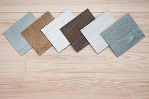 catalogo di esempio di piastrelle per pavimenti in vinile di lusso con un nuovo design d'interni per una casa o un pavimento su uno sfondo di legno chiaro. foto