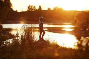 la ragazza con il cappello si trova sulla riva del fiume al tramonto foto