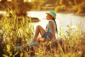 ragazza seduta sulla riva del fiume foto
