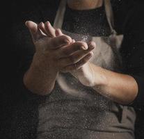 primo piano panettiere che pulisce le mani dalla farina foto