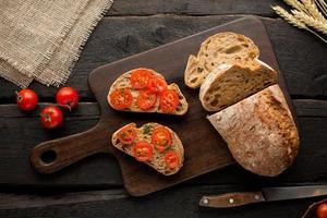 toast con pomodori e pane su una tavola su uno sfondo di legno foto
