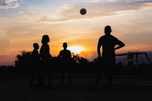 silhuoette sport d'azione all'aperto di un gruppo di bambini che si divertono a giocare a calcio di strada per fare esercizio nella zona rurale della comunità. bambini poveri e poveri nei paesi in via di sviluppo foto