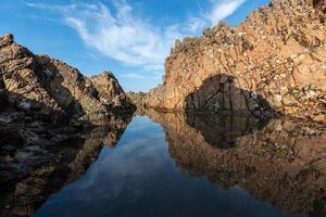l'acqua del mare tra le scogliere riflette le scogliere gialle e il cielo blu foto