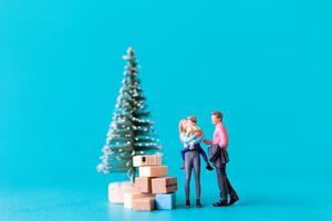 persone in miniatura, famiglia felice in piedi accanto a un albero di natale foto