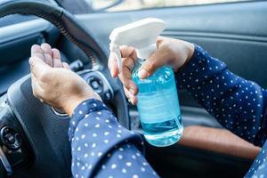 nuova normale donna lavoratrice asiatica che si lava le mani premendo gel igienizzante alcol blu per proteggere la sicurezza del coronavirus in auto. foto