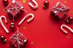 palline di natale rosse, scatole regalo e decorazioni di bastoncini di zucchero su sfondo rosso con spazio per le copie foto