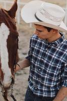 primo piano verticale di un giovane cowboy che tiene il suo cavallo foto
