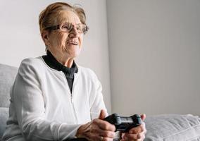 ritaglia una donna anziana con gamepad a casa foto