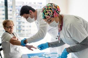 medici che prelevano campioni di sangue da un paziente anziano foto