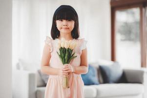 piccola figlia asiatica che tiene in mano un mazzo di fiori foto