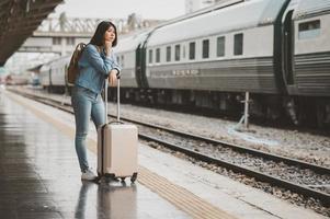 donna asiatica in attesa del treno alla piattaforma della stazione ferroviaria foto
