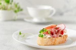 antipasto mediterraneo. panino aperto con prosciutto o jamon su piastra bianca. copia spazio foto