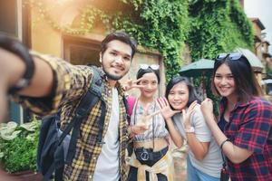 gruppo asiatico di giovani con amici zaini che camminano insieme e amici felici stanno scattando foto e selfie, tempo di relax in vacanza concetto di viaggio