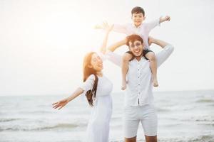 genitori attivi e persone attività all'aperto durante le vacanze estive e le vacanze con i bambini. La famiglia felice e il figlio camminano con il divertimento del mare al tramonto sulla spiaggia di sabbia. foto