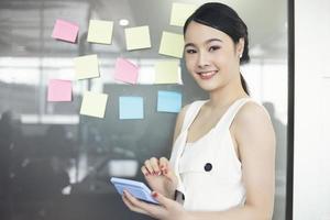 donne d'affari asiatiche che sorridono e lavorano insieme sul vetro della parete con adesivi post-it. ufficio di avvio moderno foto