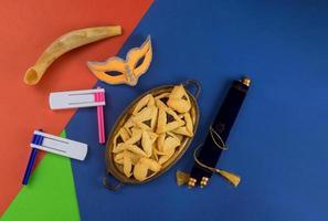 festa ebraica purim con biscotti hamantaschen hamans orecchie, maschera di carnevale e pergamena foto