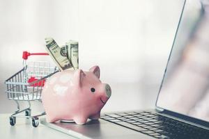 carrello della spesa e salvadanaio con laptop sulla scrivania foto