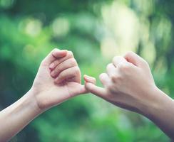 le mani si agganciano a vicenda il mignolo sullo sfondo della natura foto
