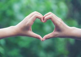 donne che creano forme di cuore con le mani foto