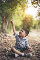 felice ragazzo seduto e pensare da solo nel parco foto
