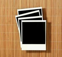 vintage storte vecchie pellicole polaroid distesi su sfondo di bambù foto
