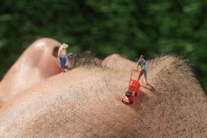 piccole persone che tagliano i capelli dal viso di un uomo foto