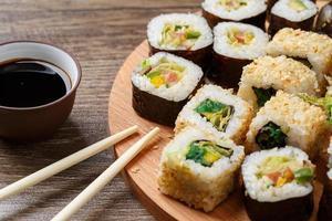 involtini di sushi con salmone e cerimonia del tè caldo sul tavolo di legno nero foto