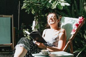 donna che ride mentre legge un libro mentre è sdraiata su una sedia durante una giornata di sole, copia spazio, concetti di relax e hobby, social network foto
