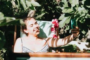 giovane donna che si fa un selfie mentre si rilassa in un giardino durante una giornata di sole, concetto di social network, ragazza felice foto