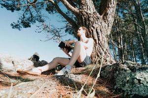 giovane maschio hippie che legge un libro, ampia angolazione, social network, vibrazioni estive stile di vita rilassato foto