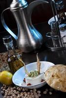 hummus cremoso fatto in casa con olio d'oliva e patatine fritte foto