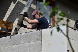 cementare le pareti utilizzando una macchina a pompa durante la costruzione della casa foto