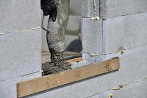 dettaglio di una pompa per calcestruzzo da cui il calcestruzzo viene versato nelle pareti del cantiere foto