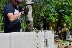 un lavoratore del cemento in un cantiere cementa le pareti usando una macchina foto