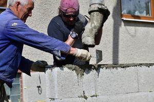 una combinazione di lavoro manuale da parte di un muratore e una pompa per calcestruzzo mentre si posiziona il cemento nei muri foto