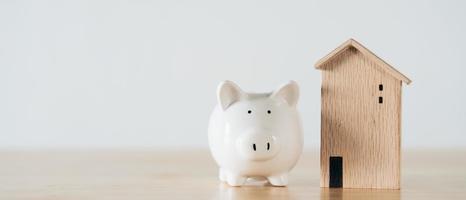 casa in legno con salvadanaio bianco sul tavolo di legno. risparmio di denaro per l'acquisto di casa, concetto di mutuo per la casa del piano finanziario. foto
