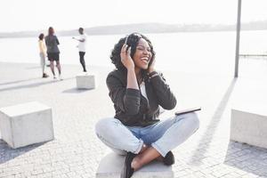 ritratto di una giovane e bella ragazza afroamericana seduta sulla spiaggia o sul lago e ascoltando musica nelle sue cuffie foto