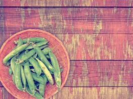 piselli verdi sullo sfondo di legno foto