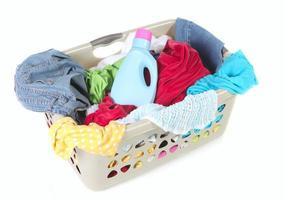 cesto della biancheria pieno di vestiti sporchi e ammorbidente foto
