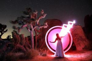 persona dipinta di luce nel deserto sotto il cielo notturno foto