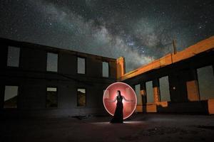 bellissima modella in posa nel deserto di notte con la via lattea foto