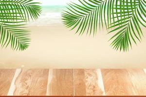 piano del tavolo in legno su sfondo sfocato spiaggia con foglia di palma verde, concetto estivo foto