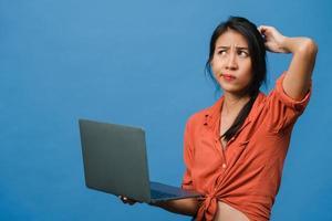giovane donna asiatica che usa il computer portatile con espressione negativa, urla eccitate, piangi emotivamente arrabbiato in un panno casual e stai isolato su sfondo blu con spazio vuoto per la copia. concetto di espressione facciale. foto