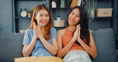 adolescente coppia donne asiatiche sentirsi sorridenti felici e guardando la telecamera mentre si rilassano nel soggiorno di casa. Videochiamata allegra delle signore del compagno di stanza con l'amico e la famiglia, concetto di stile di vita della donna a casa. foto