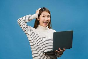 giovane donna asiatica che utilizza il computer portatile con espressione positiva, sorride ampiamente, vestita con abiti casual sentendosi felici e in piedi isolato su sfondo blu. felice adorabile donna felice esulta successo. foto