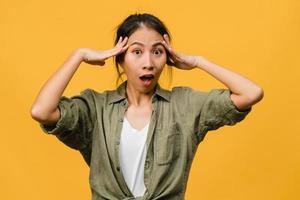 la giovane donna asiatica si sente felice con l'espressione positiva, gioiosa sorpresa funky, vestita con abiti casual e guardando la telecamera isolata su sfondo giallo. felice adorabile donna felice esulta successo. foto